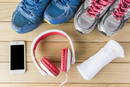 Sportschoenen met een fles water en een koptelefoon op houten achtergrond