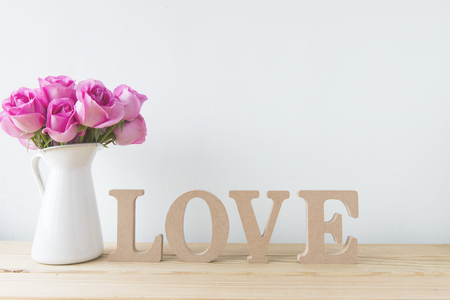 silliness: Pretty flower with a wooden love on the white wall