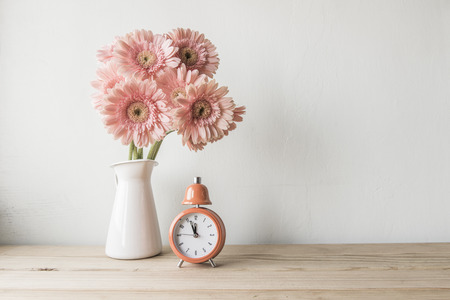 book shelves: flowers and  alarm clock on a white wall shelf Stock Photo