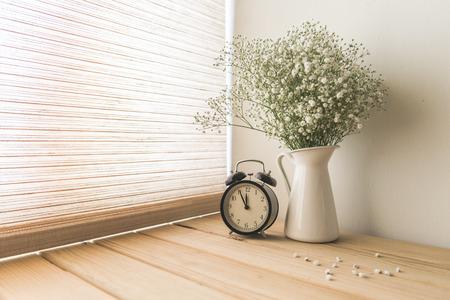 bloemen en wekker op een witte muur plank