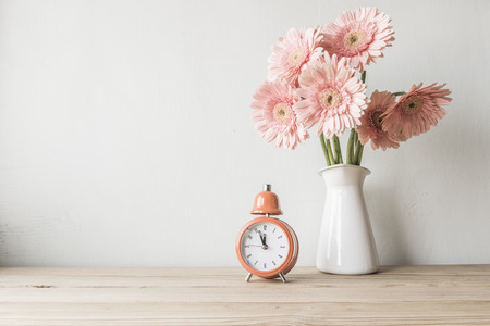 decorative objects: flowers and  alarm clock on a white wall shelf Stock Photo
