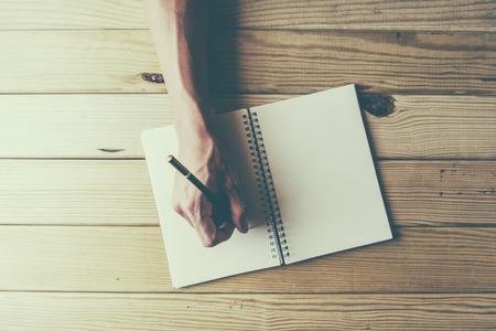 mâle, main, écrit dans un grand bloc-notes sur une table en bois