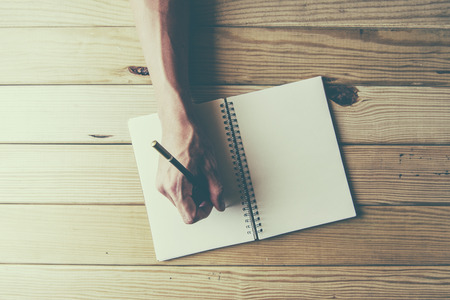 write: male hand is writing in a big notepad on a wooden table