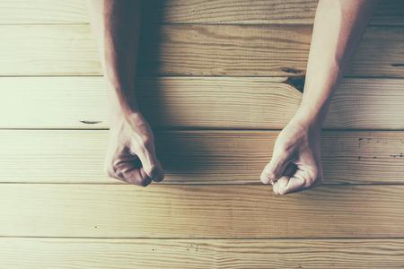 enojo: Puños femeninos apretados en una mesa de madera en la ira