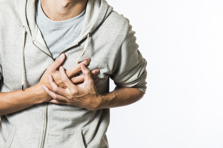 palpitation: man feeling heart pain and holding her chest Stock Photo