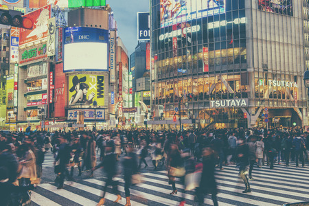 scramble: TOKYO, JAPAN - APRIL 04, 2016: Pedestrians walk at Shibuya Crossing during the holiday season. The scramble crosswalk is one of the largest in the world. Editorial