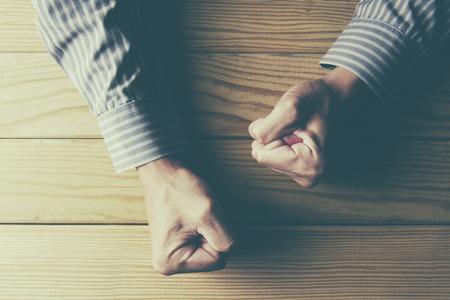 enfado: hombre con los puños apretados en una mesa de madera en la ira