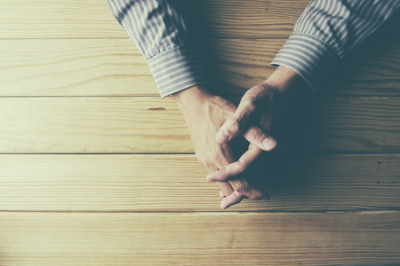 Close up on male hands folded in prayer at a wooden table Stock Photo