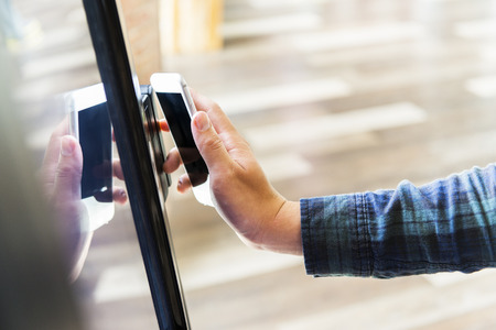ticketing: man paying by cellphone on ticketing machine Stock Photo