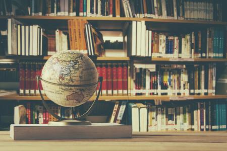 ぼかし抽象的なキャンパス図書館背景を持つ古い時代の木のテーブルに本教科書の世界モデル
