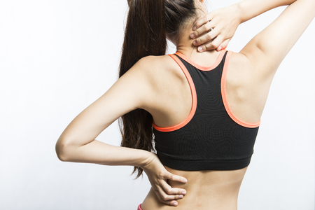 Back view of athletic young woman in sportswear touching her neck and lower back muscles by painful injury Banque d'images