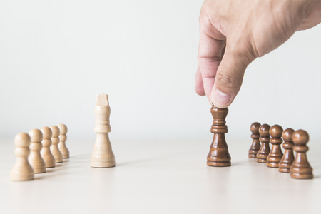 team from behind: Business man moving chess figure with team behind - strategy or leadership concept Stock Photo
