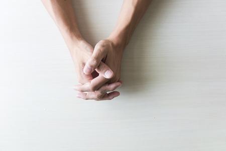 Gros plan sur les mains mâles pliées en prière à la table Banque d'images - 65797290