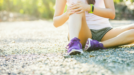 Runner sport knee injury. Woman in pain while running in park