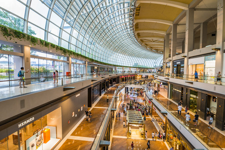 buying time: SINGAPORE - CIRCA AUG 2017: Luxury expensive brands shops promenade and customer inside of modern huge shopping mall The Shoppes at Marina Bay Sands