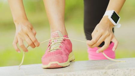 young asian woman tying shoelace on forest trail