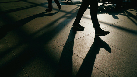 Long shadows of people walking in a street with sunlight in the background