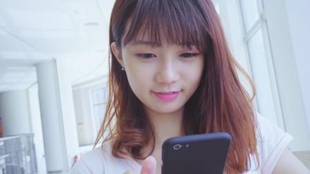 jonge Aziatische vrouw met behulp van smartphone