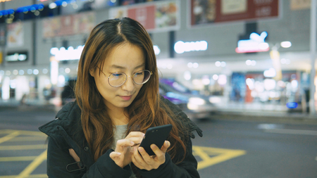business woman use phone in the city at night