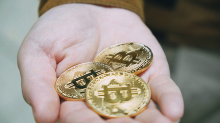 Man hands holding crypto currency BTC Bitcoin coins