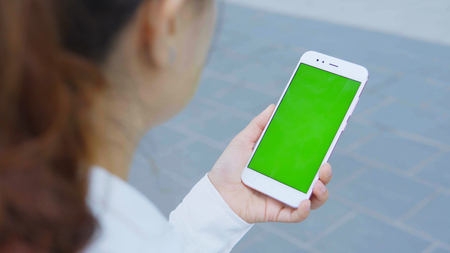 Woman using smartphone with green screen on the street.