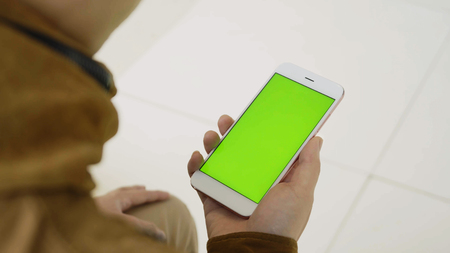man using smartphone with green screen on the street.
