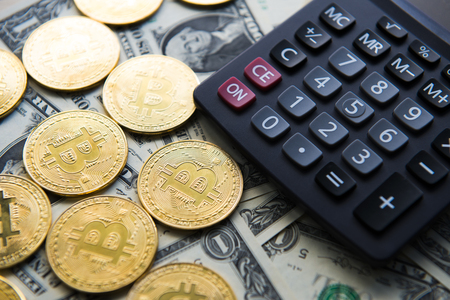 Business woman using counting and gold ingots with bitcoin on calculator Banque d'images
