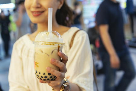 Woman drinks pearl milk tea at Taiwan night market Stock Photo - 107777564