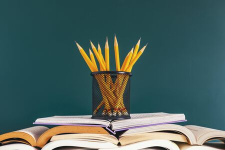 Pencils in container and opened books on green background
