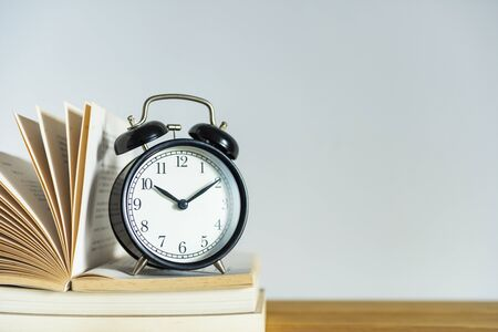 Alarm clock and books on white background
