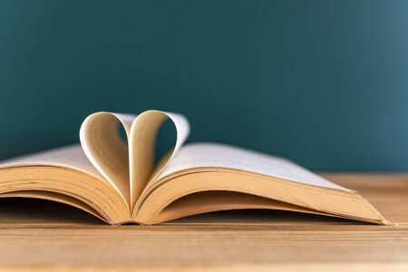 Book with opened pages and shape of a heart on green background