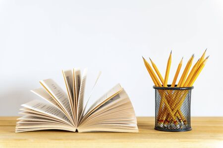 Flipping book pages and pencils in container on white background Stockfoto