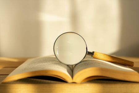 Magnifier and opened book on white background