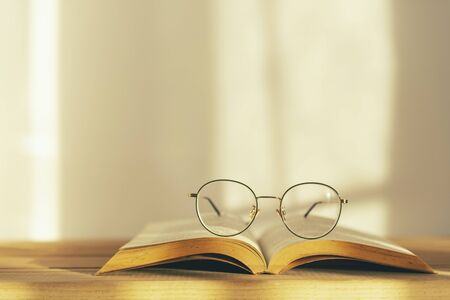 Reading glasses on top of opened book on white background