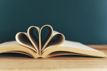 Book with opened pages and shape of two hearts on green background Stockfoto