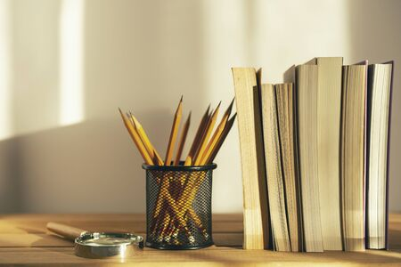 Magnifier, pencils and books on white background