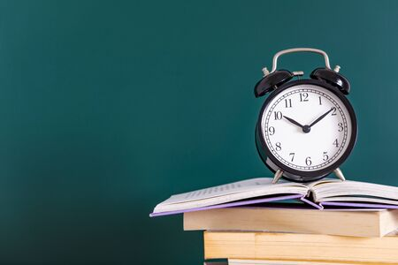 Alarm clock and books on green background Stockfoto