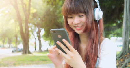 Young Asian Woman Listen To Music With Earphone And Her Smart Phone Stockfoto