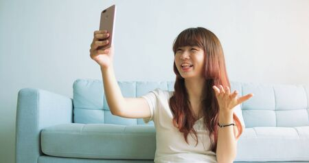 Young Asian Woman video At Home. Stockfoto