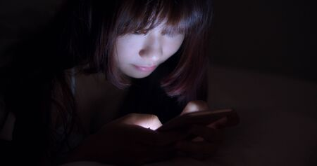 Woman Using Cellphone In Bed At Night