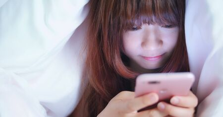Woman Use Phone And Smile Happily On The Bed Stockfoto