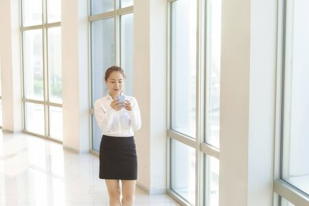 Pretty asian business woman holding mobile phone