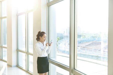 Pretty asian business woman using mobile phone