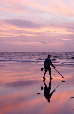 A photo of a man using a metal detector on the beach at sunrise at Tybee Island, Georgia.
