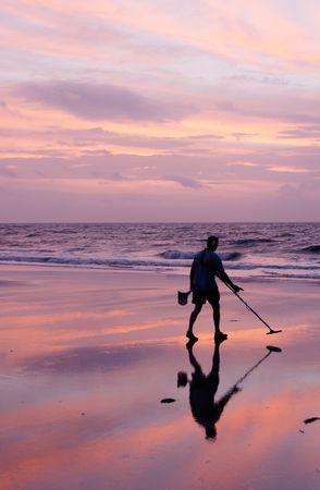 tybee island: A photo of a man using a metal detector on the beach at sunrise at Tybee Island, Georgia.