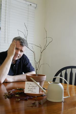 A man looking perplexed after realizing that he did not water the plant. Stock Photo - 5643405