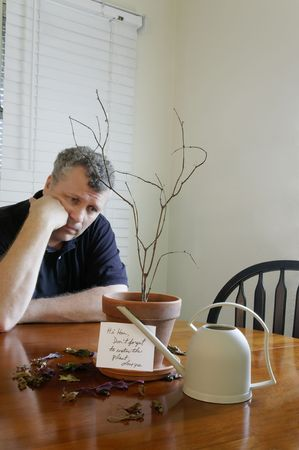 A man looking sad after realizing that he forgot to water his wifes plant.