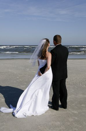 A bride and a groom at the ocean.