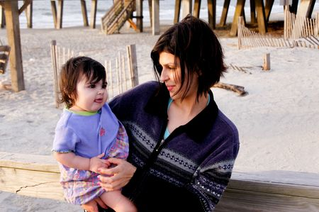 A hispanic mother and her baby at the beach.