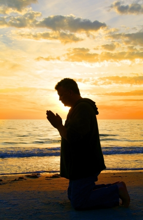 meditation pray religion: Man kneeling and praying at the ocean with the sun framing his head  Stock Photo